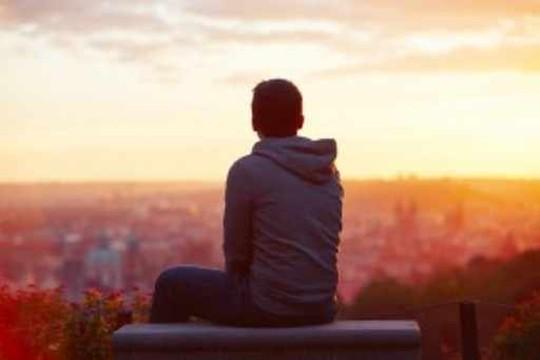 若い男が日の出を見ている