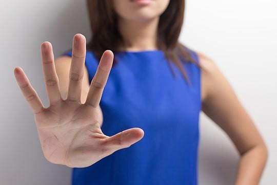 手のひらを差し出してNOを表現する女性